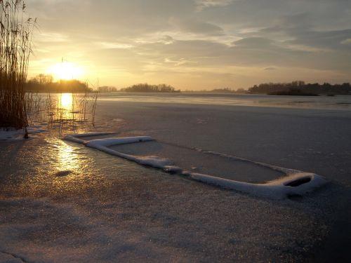sunset frozen lake frozen boat