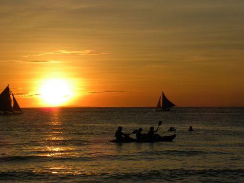 sunset sailing boats