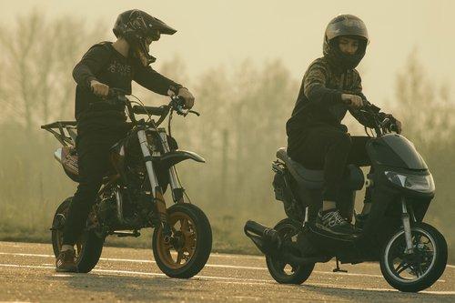 teenagers on mopeds  scooter  helmet