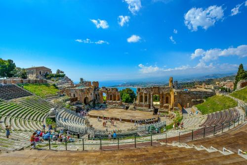 theatre,theater,greek,italy,taormina,sicily,ruins,ancient,seating,view,mediterranean,blue,sea,boats,shore,sky,old,scenic,vista,round,arena,coastal,travel,vacation,tourism