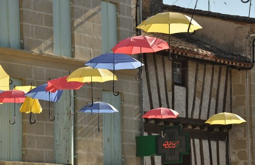 umbrellas  village street  sun
