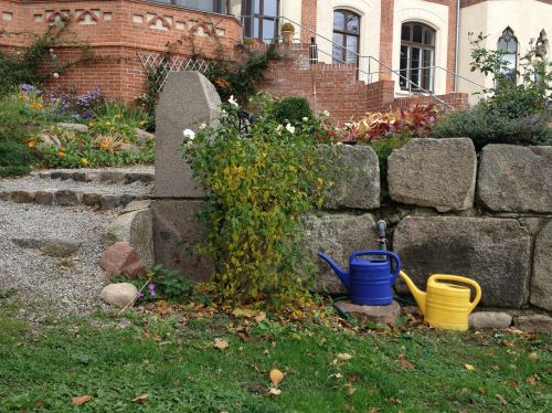 watering can garden stone wall