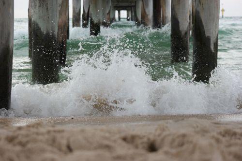 waves breaking waves under a pier beach waves