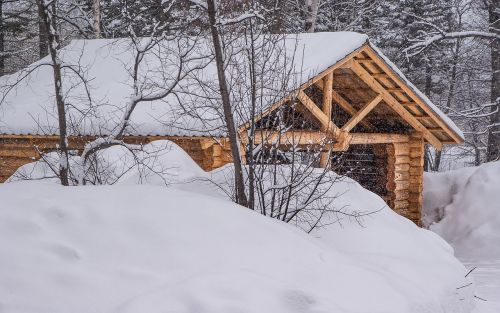 wooden house logs snowfall