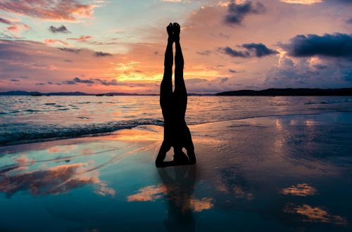 yoga stand in hands silhouette sunset beach zen position by the sea